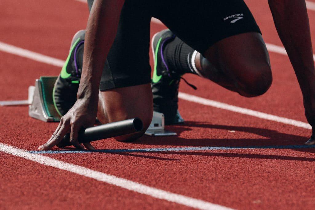 Imagem ampliada de um atleta ajoelhado, momentos antes de dar início à corrida.