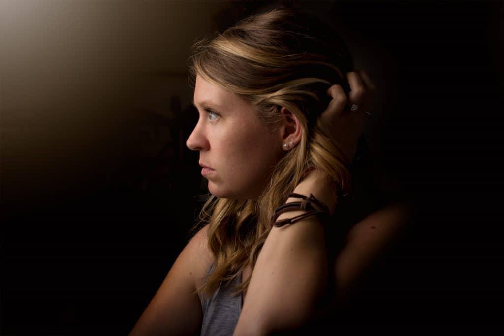 Mulher vista de perfil, mexendo em seu cabelo cabelo com a mão, com expressão infeliz.