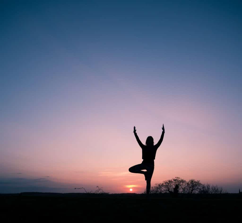 Silhueta de mulher em posição de meditação com sunset ao fundo