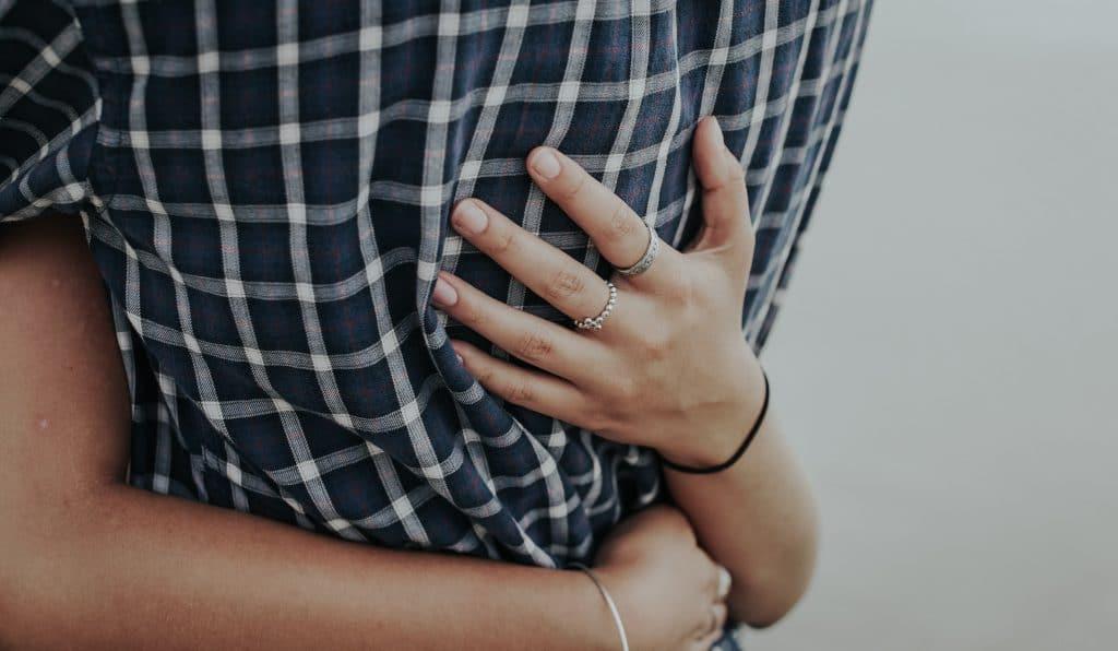 Mãos nas costas de alguém sendo abraçado