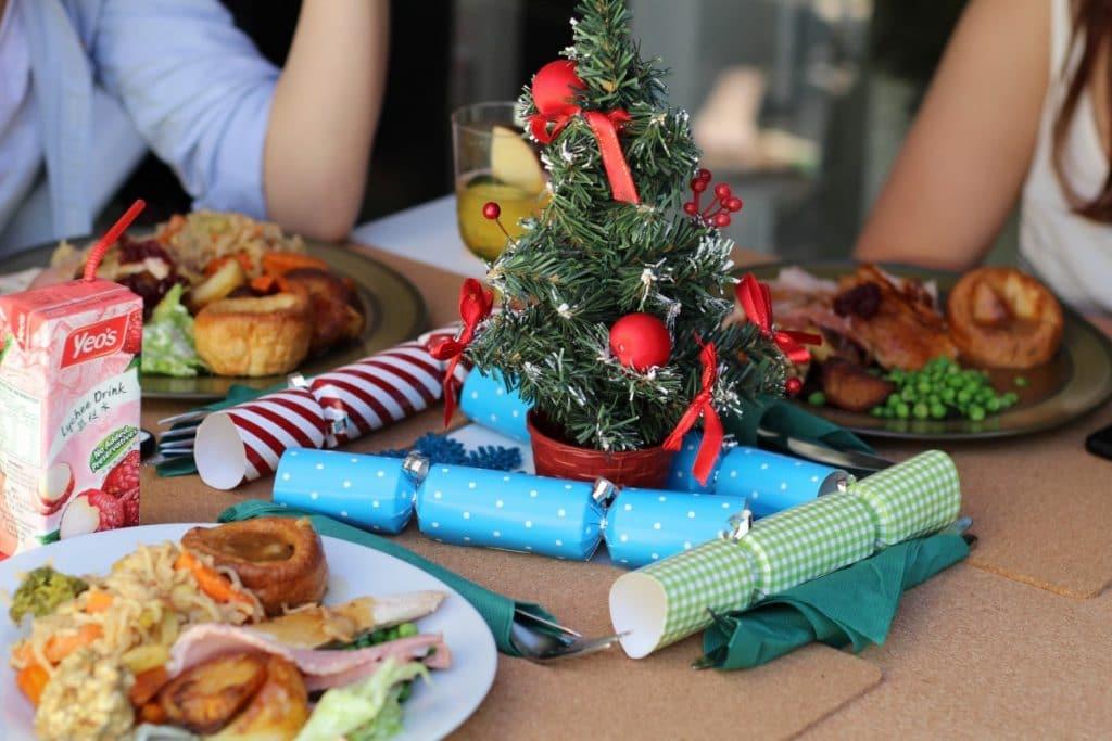 Três pratos de comida cheios em uma mesa com uma árvore de Natal em miniatura no centro.