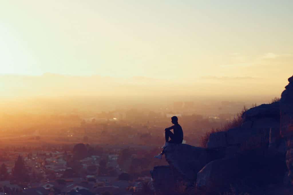 Silhueta de homem sentado em uma montanha, ao pôr do sol, observando a paisagem.