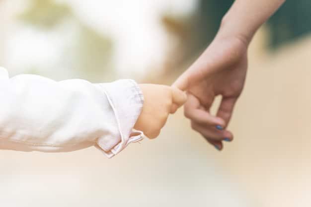 Mãe e filho de mãos dadas.