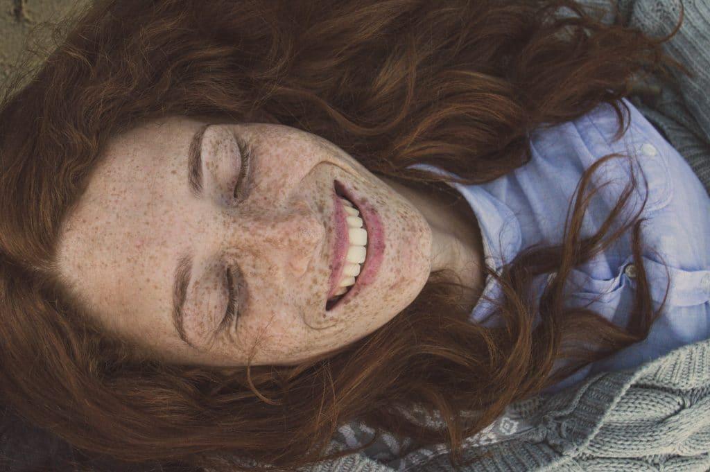 Mulher com sardas no rosto de olhos fechados e cabelo solto