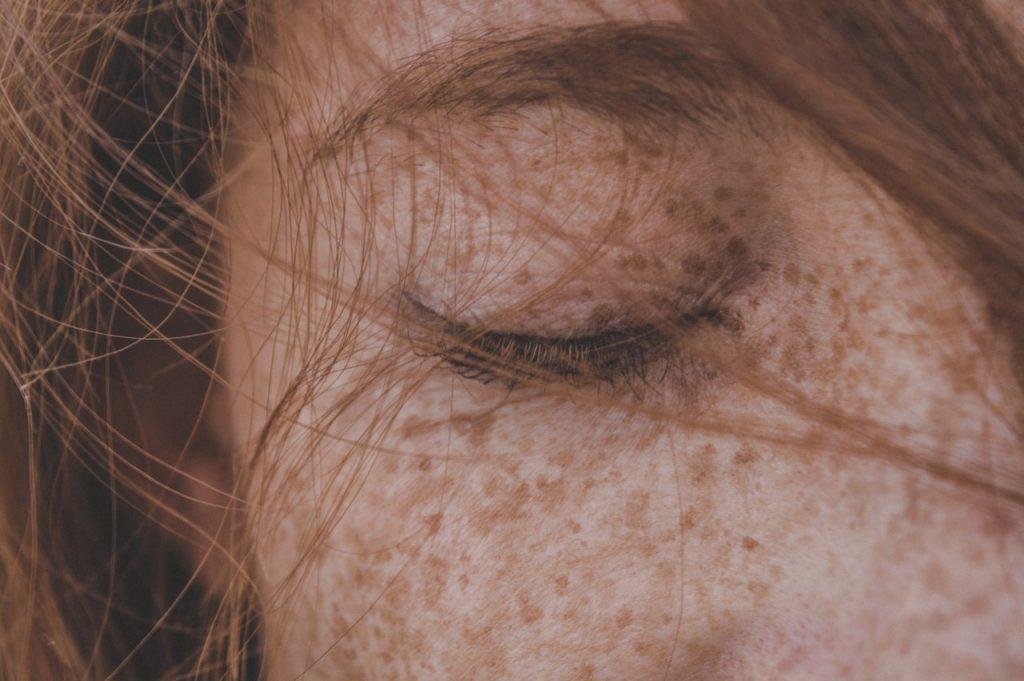 Mulher ruiva de olhos fechados e cabelos esvoaçantes sobre o rosto.