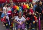 Dois palhaços ao lado de uma senhora de cadeira de rodas