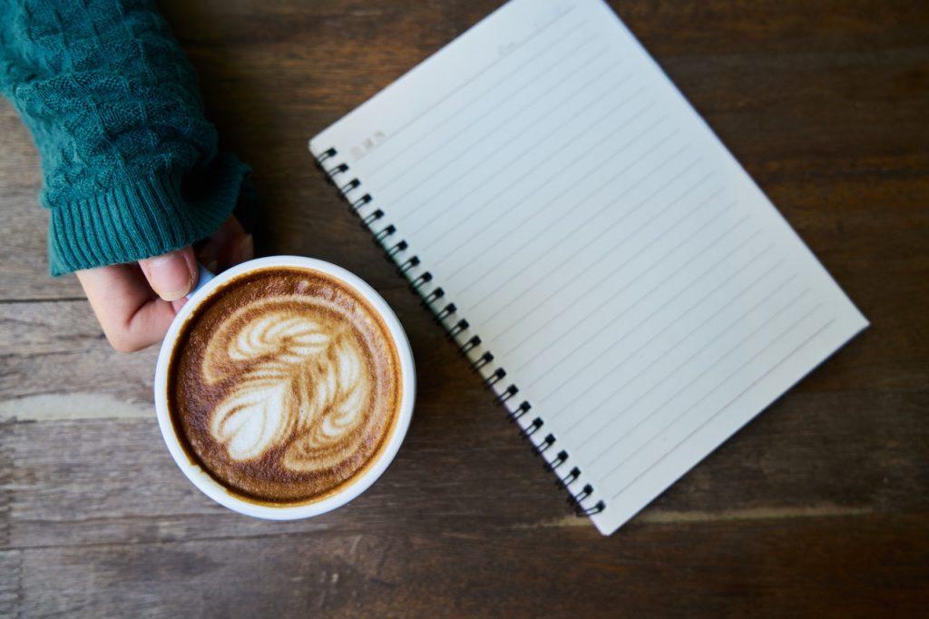 Pessoa segurando uma xícara de café, em uma mesa de madeira, ao lado de um caderno de anotações.