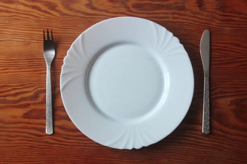 Prato branco vazio em cima de uma mesa de madeira, com faca e garfo nos lados.