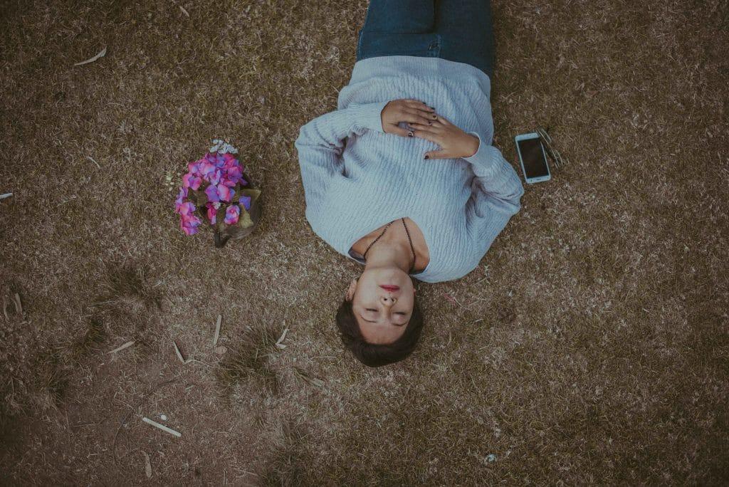 Mulher deitada em grama seca de olhos fechados