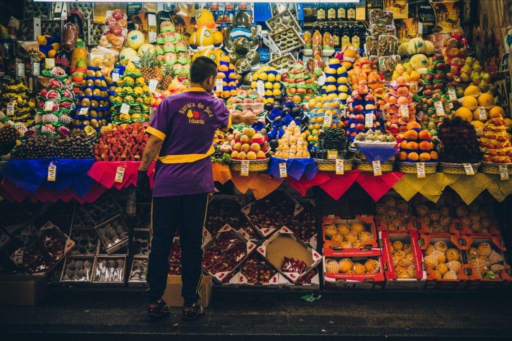 Homem de costas arrumando frutas em prateleira