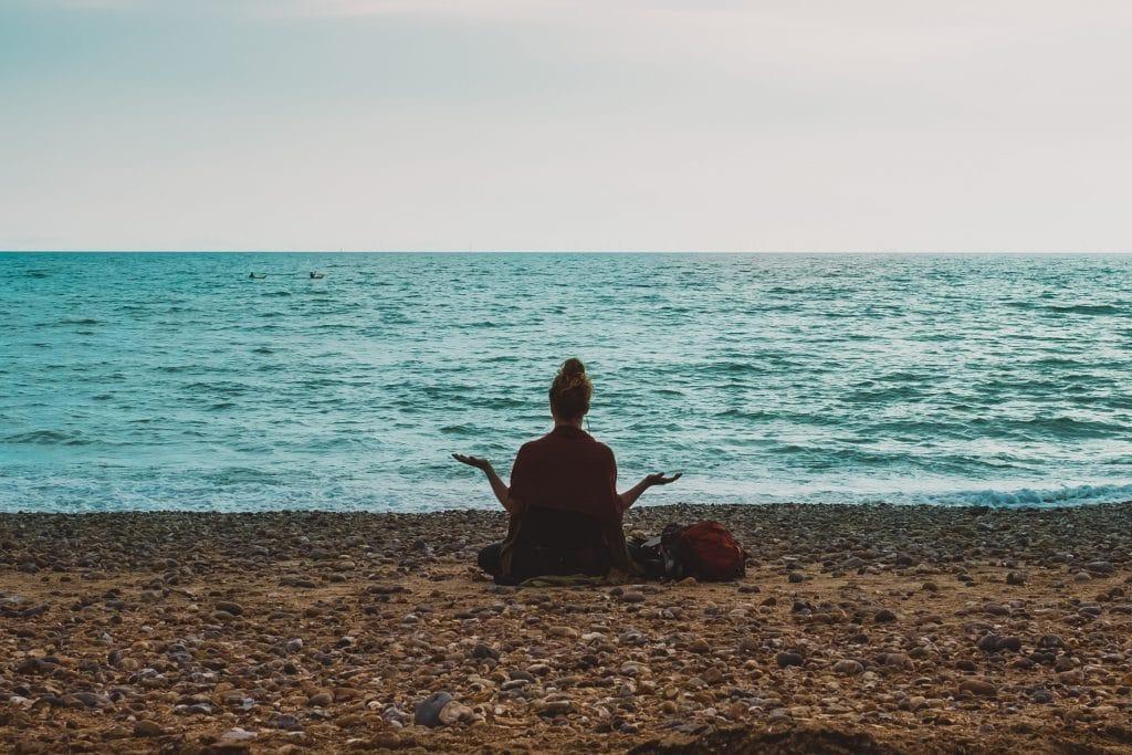 Silhueta de uma mulher de costas, na praia, meditando sentada na areia, de frente para o mar.