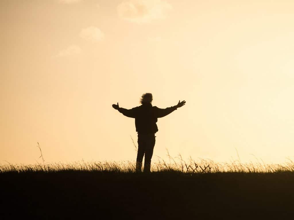 Silhueta de uma pessoa em pé em um campo, com os braços estendidos em sinal de gratidão.