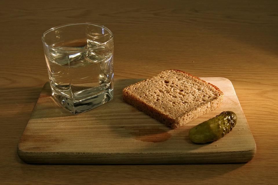 Copo com água, fatia de pão integral e picles em cima de uma bandeja de madeira.