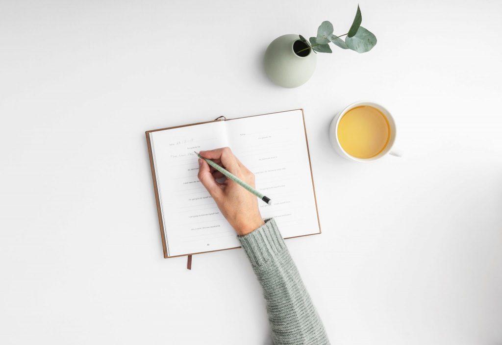 Foto da mão de uma menina escrevendo em um caderno. Ao lado há uma xícara com chá e uma plantinha.