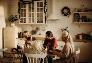 Família sentada ao redor de uma mesa para celebrar a ceia de Natal.