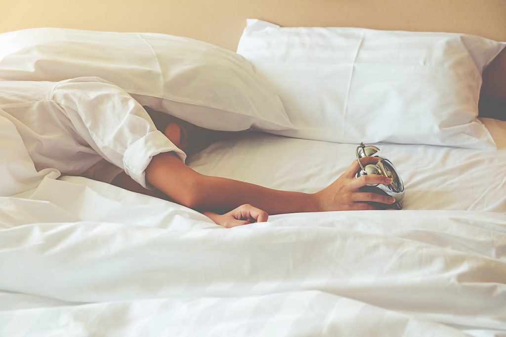 Mulher deitada na cama desligando o relógio despertador.