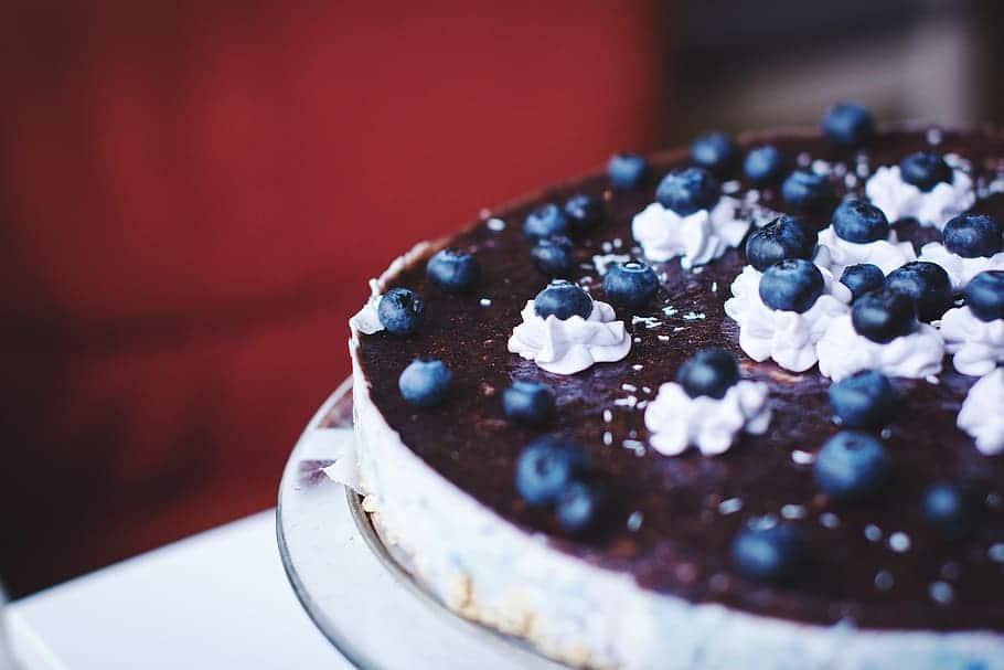 Cheesecake com calda de mirtilo, e mirtilos espalhados em cima.