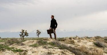 Homem segura uma maleta em paisagem natural, onde aparenta estar perdido.