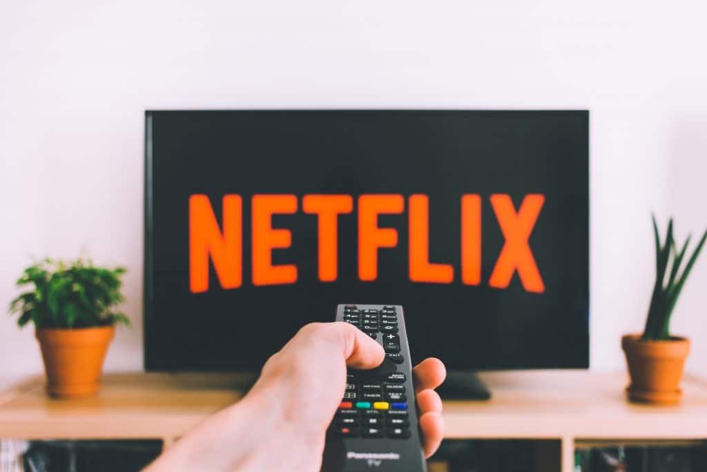 Mão com controle apontando para TV com abertura Netflix