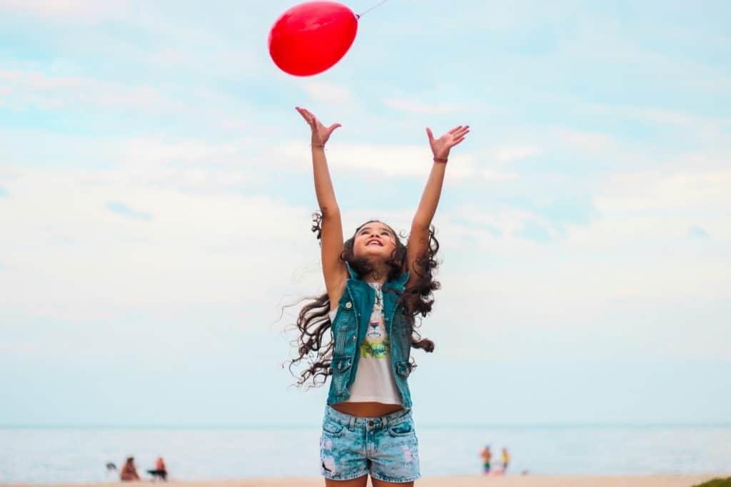 Garota tentando alcançar balão.