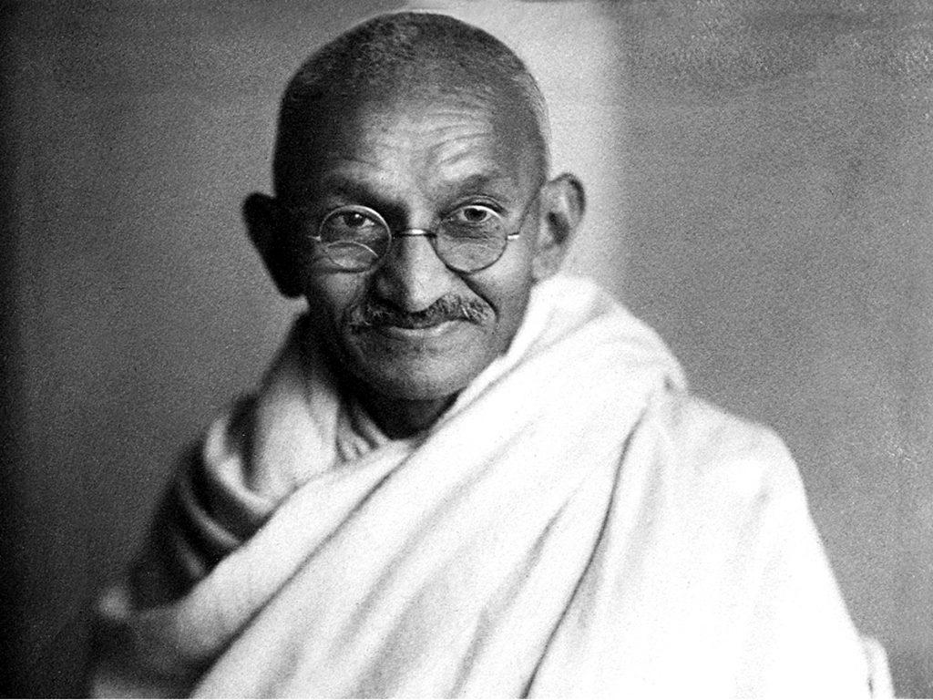 Fotografia em preto e branco de Mahatma Gandhi, de óculos e roupas tradicionais brancas, sorrindo para a câmera.