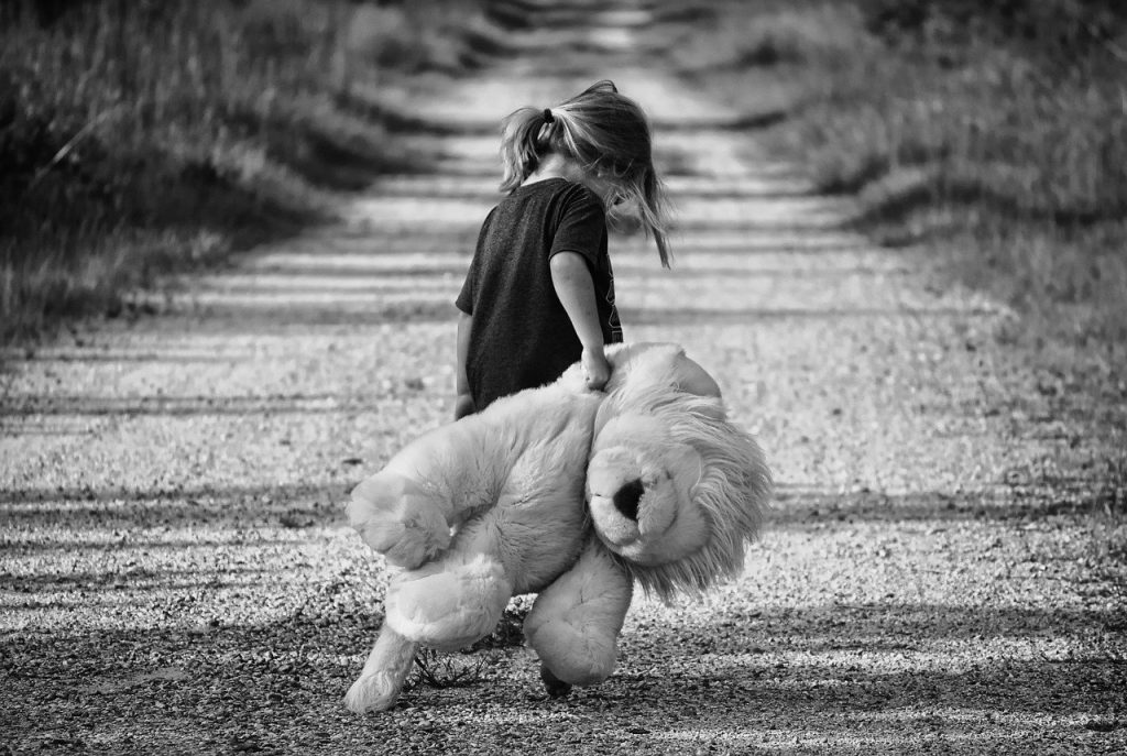 Menina com a cabeça baixa anda arrastando um urso de pelúcio grande atrás dela, por uma estrada de terra.