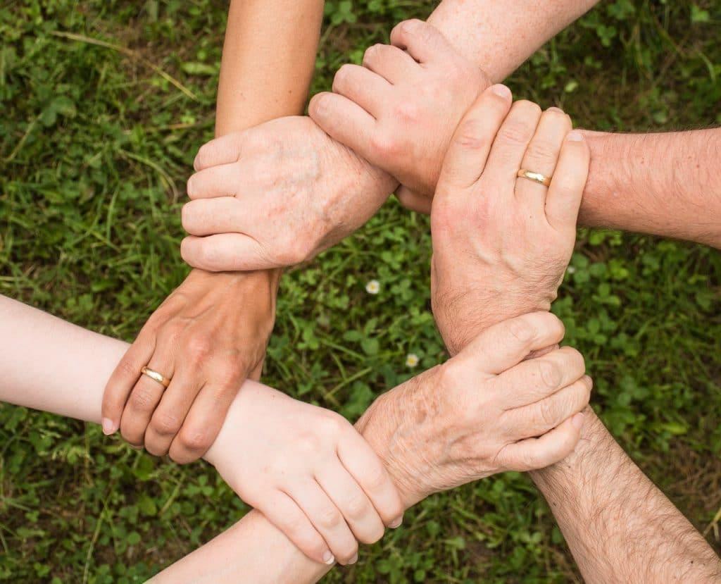Grupo de pessoas segurando as mãos uns dos outros sobre um fundo verde com gramado.