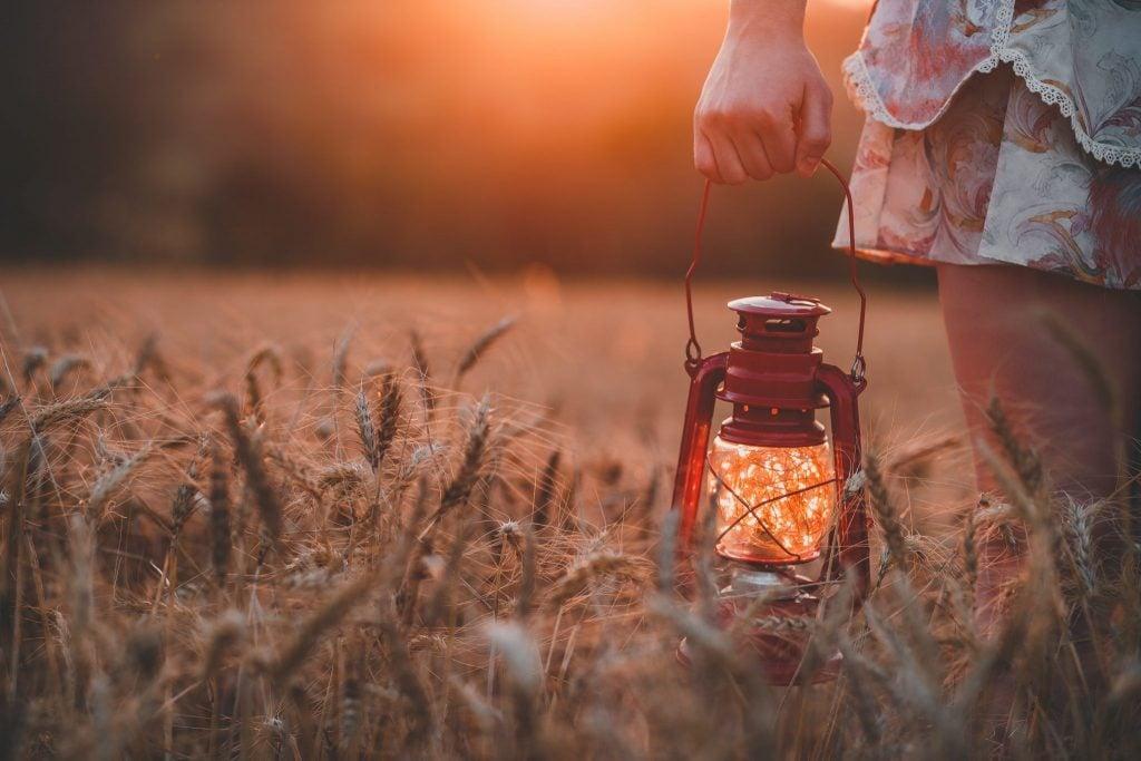 Mão segurando lamparina em campo de trigo com luz do sol refletindo