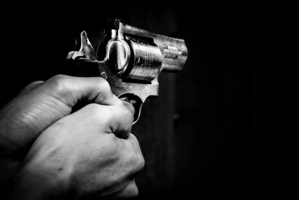 Foto em preto e branco de uma pessoa segurando uma arma com as duas mãos e o dedo indicador esquerdo no gatilho. O fundo da imagem é completamento preto.