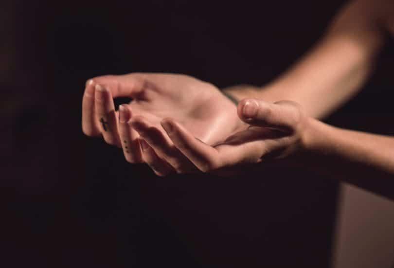 Mãos de uma mulher estendidas em sinal de oração.