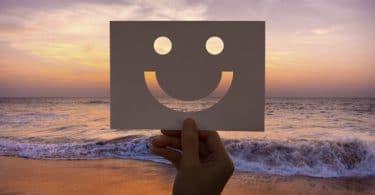 Papel cortado em forma de um rosto feliz.