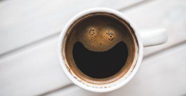 Xícara de café vista de cima, com a espuma do líquido formando um rosto sorridente.