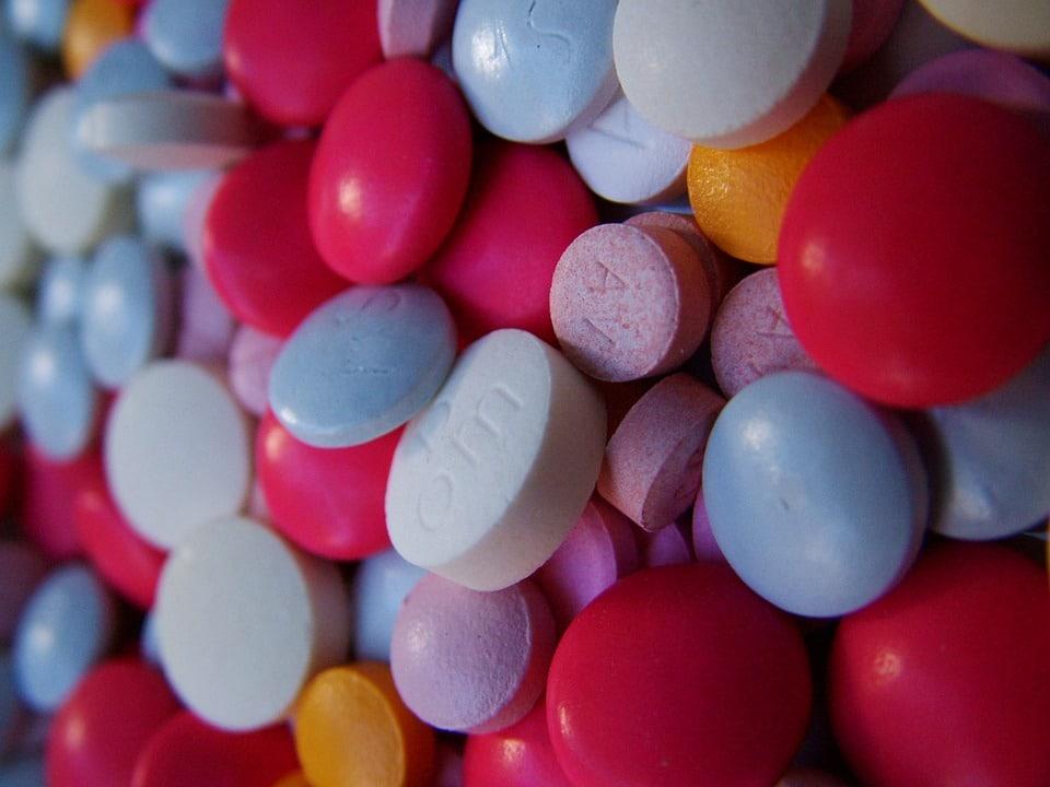 Muitos comprimidos de cores variadas juntos, com a foto bem focada neles.
