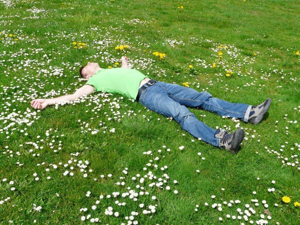 Homem deitado em gramado cheio de pequenas flores brancas e amarelas.
