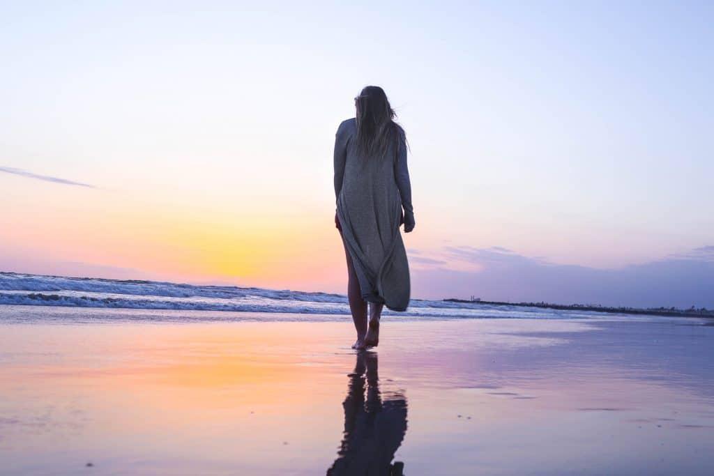 Mulher caminhando em praia sentido o mar com pôr-do-sol ao fundo