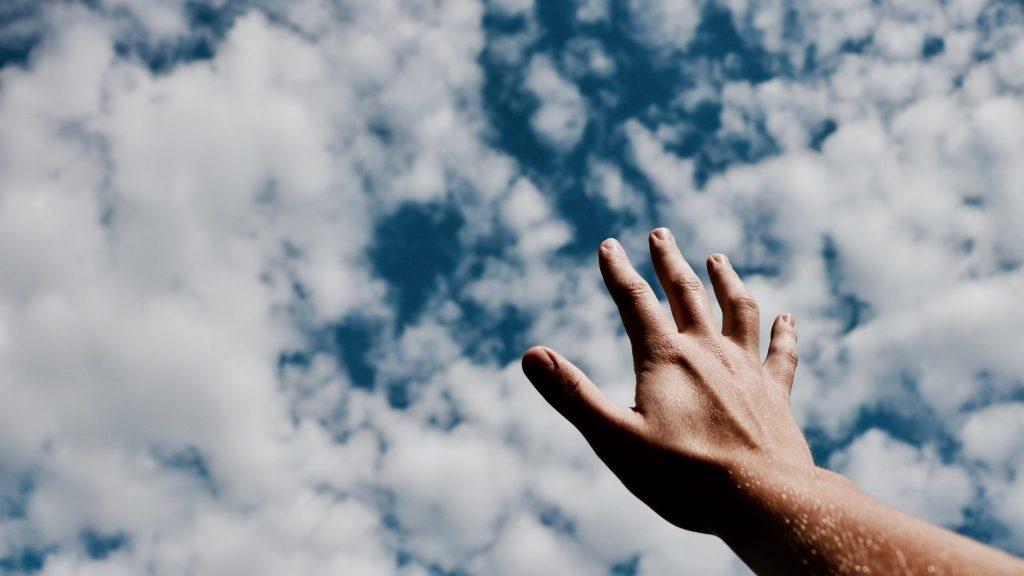 Mão para o céu com nuvens ao fundo