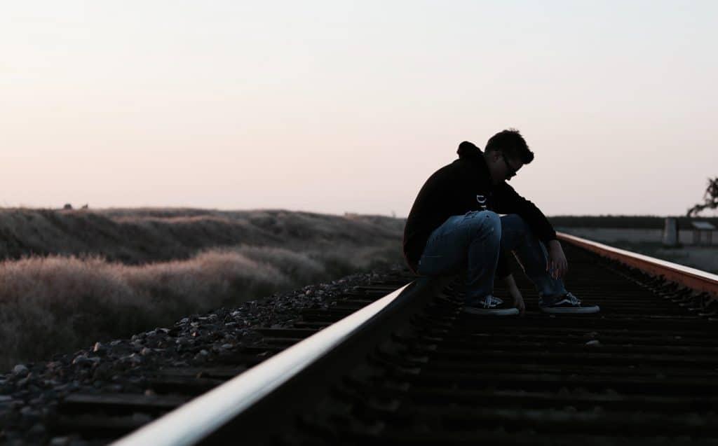Garoto sentado em trilho de trem com cabeça abaixada