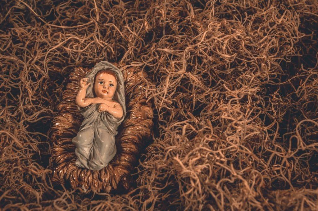 Boneco em miniatura de Jesus quando bebê, enrolado em um tecido azul, sobre montes de feno.