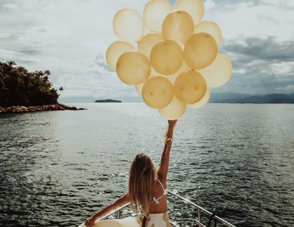Mulher segurando bexigas de aniversário em uma lancha no mar
