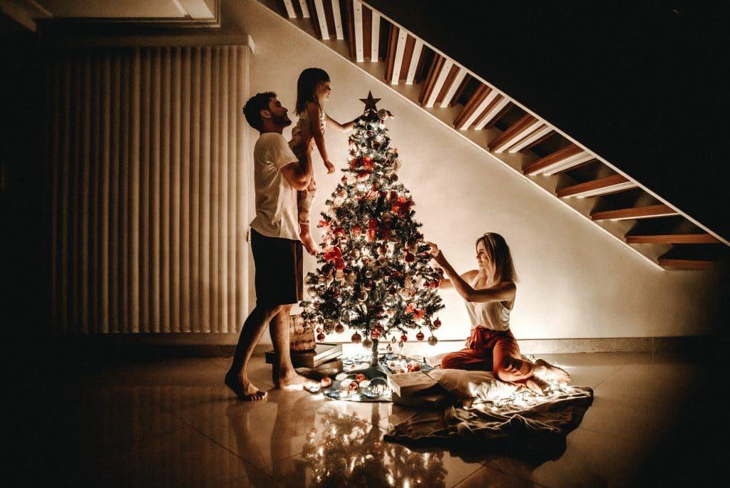 Família com mãe, pai e filha criança montando uma árvore de Natal.