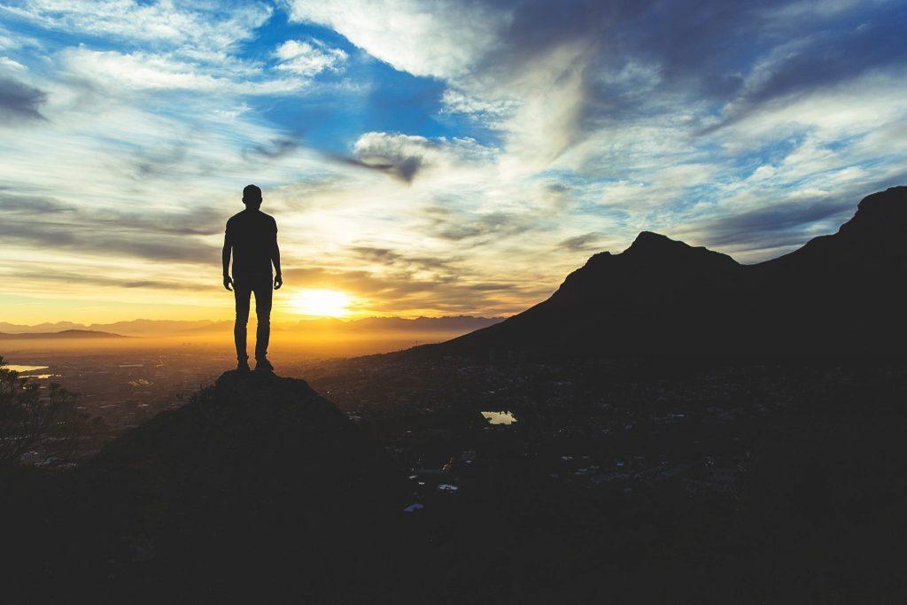 Silhueta de homem em montanha olhando pôr-do-sol