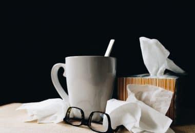 Lenços de papel, óculos e caneca em cima de uma mesa de madeira.