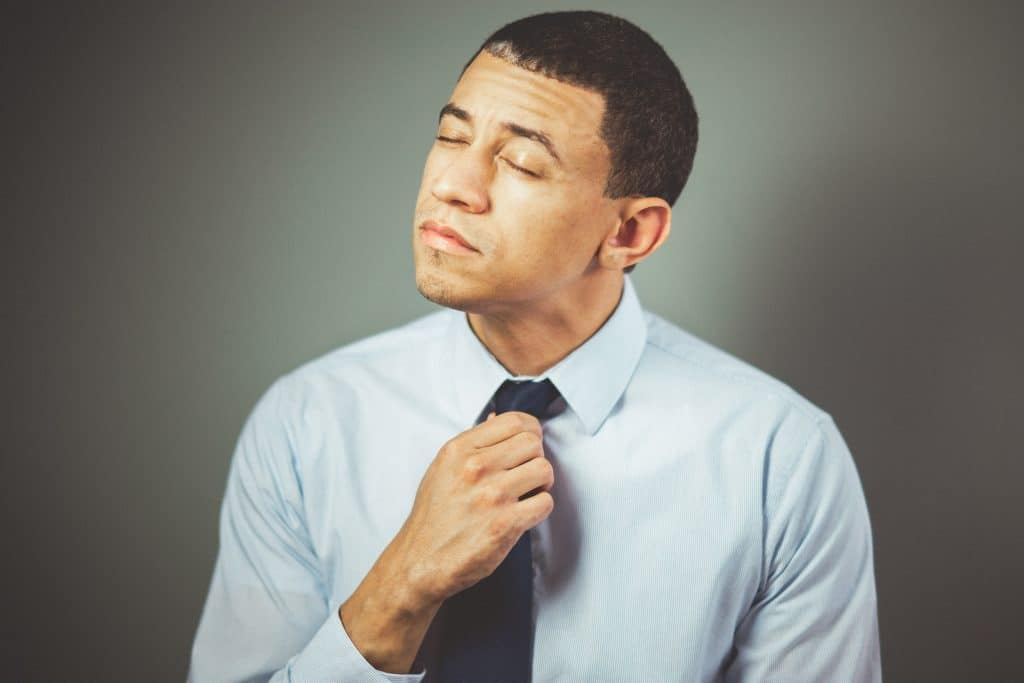 Homem com mão na gravata e olhos fechados tentando relaxar