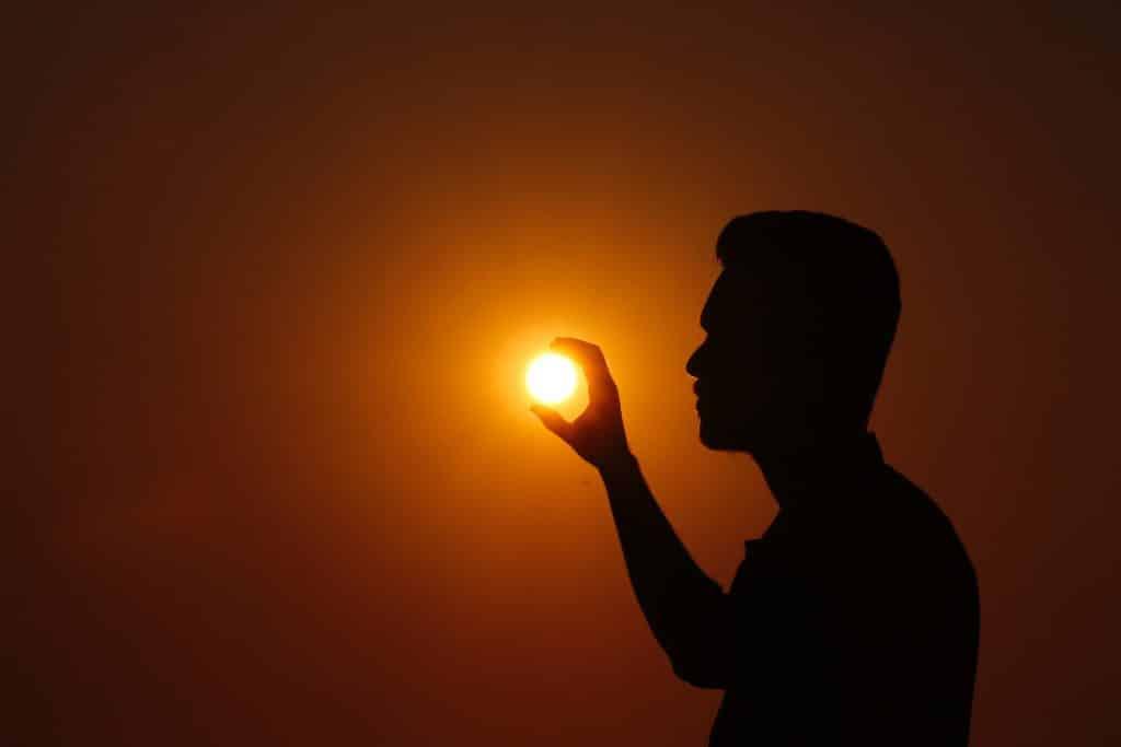 Silhueta de homem com sol ao fundo como se ele estive segurando