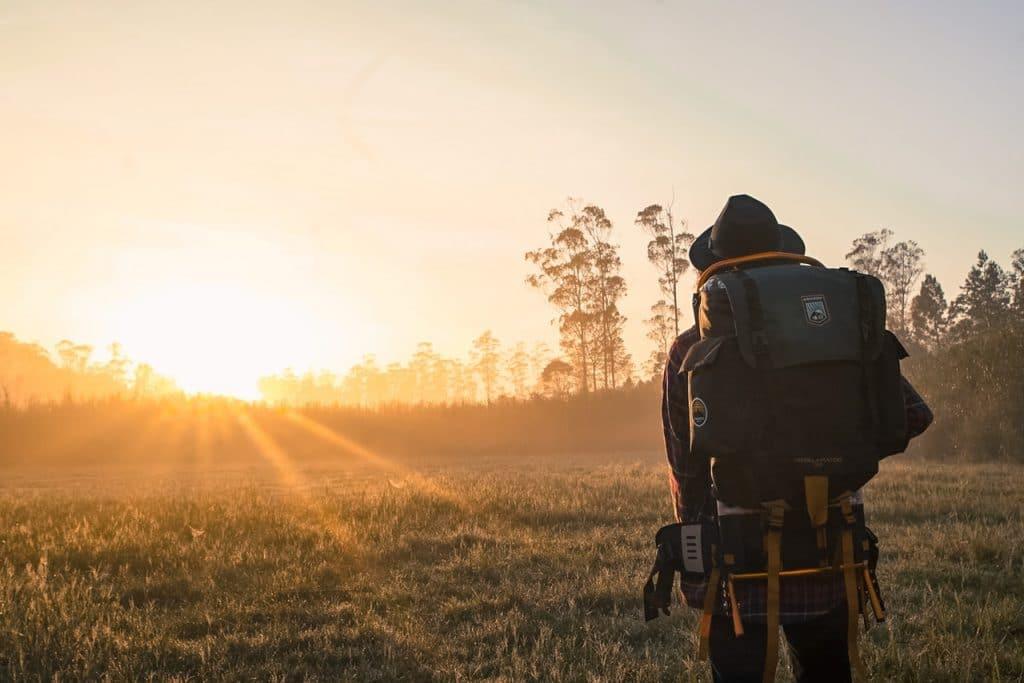 Pessoa viajante com chapéu e mochila nas costas olha para o nascer do sol.