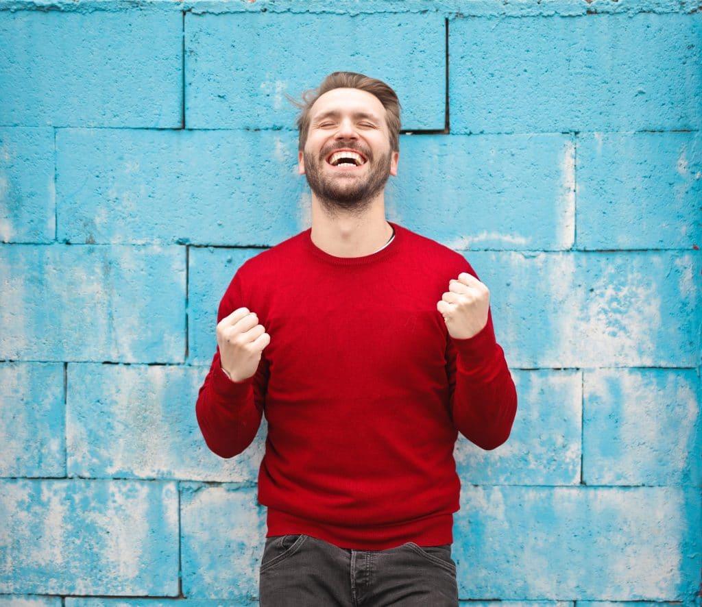 Homem de sorriso aberto comemorando