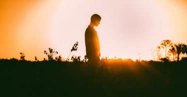 Silhueta de pessoa com sol refletindo ao fundo