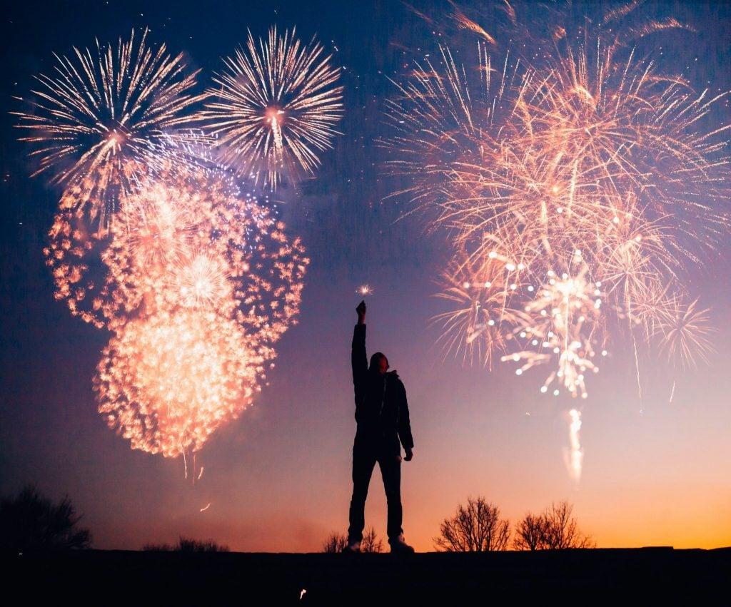 Homem segurando vela estrelinha com fogos artificiais ao fundo estourando