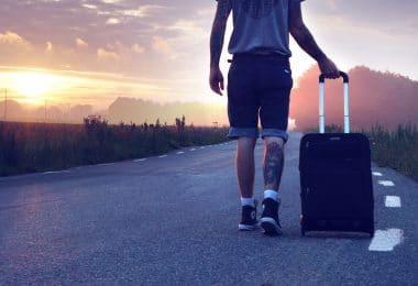Homem caminhando em estrada com mala de costas