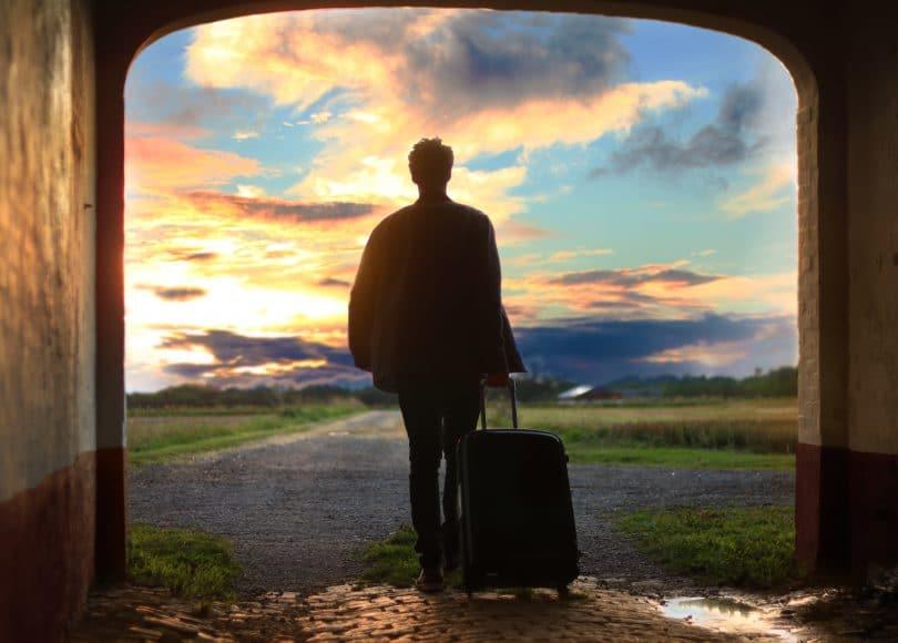 Silhueta de pessoa com mala de viagem com céu ao fundo